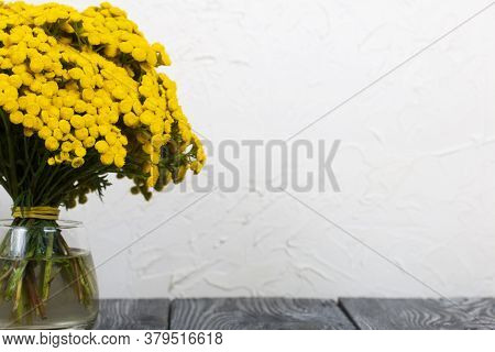 A Bouquet Of Tansy In A Glass Goblet. On A White Background.