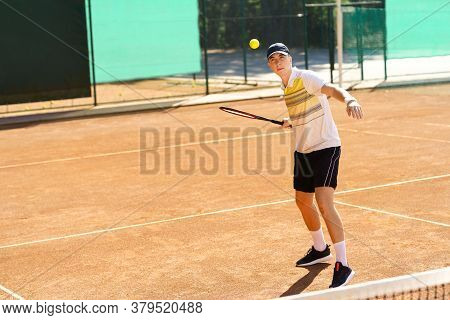 Young Tennis Player Hitting The Ball. Sport And Health