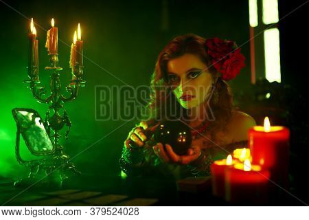 Magnificent fortune teller woman reading future on magical crystal ball.
