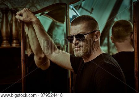 Portrait of a handsome brutal mature man with short hair and bristles wearing trendy sunglasses  against the background of the mirror in the apartment. Manly style. Optics for men.