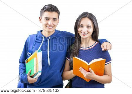 Young And Happy Latin Students Studying Standing On White Background. Looking At The Camera