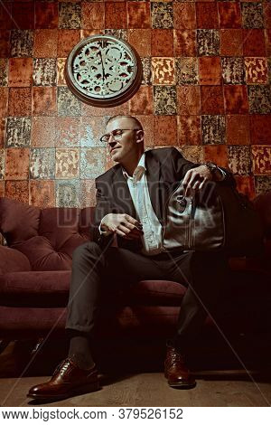 Portrait of a respectable middle-aged man in an expensive suit and glasses sitting on a sofa with luggage bag in a luxurious apartment. Success and rich lifestyle.