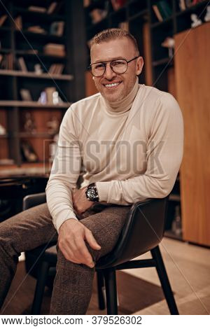 Portrait of a respectable middle-aged man in an expensive suit and glasses sitting on a chair in a luxurious apartment. Success and rich lifestyle.