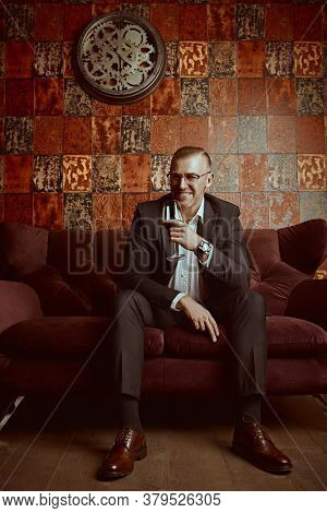 Portrait of a respectable middle-aged man in casual clothes and glasses drinking red wine in a luxurious apartment. Success and rich lifestyle.