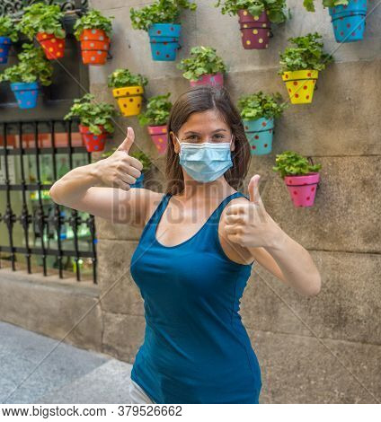Young Woman Wearing Surgical Mask On Face Showing Thumb Ups Happy To Be Outdoors. Coronavirus Spread