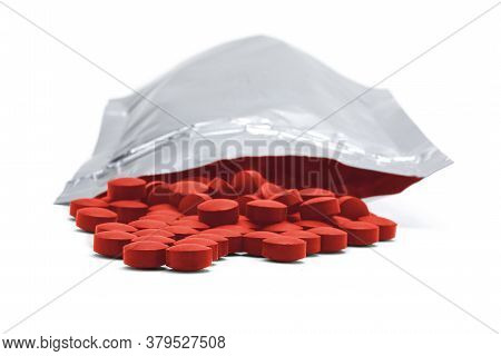 Medicine Pills, Vitamins Of Red Color In A Resealable Aluminum Bag On White Background
