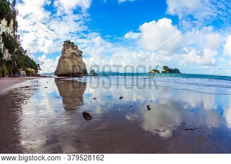 Travel to New Zealand. Ocean tide in the Cathedral Cove. Mirror reflections of clouds in wet sand. The far end of the earth. The concept of exotic, ecological and photo tourism