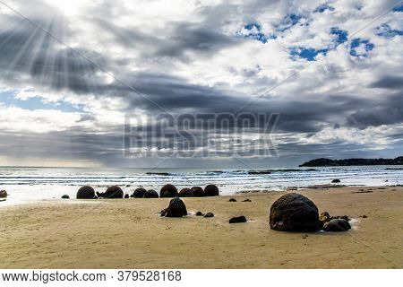 Moeraki boulders is a group of huge stones and their remains. Low tide in ocean. The South Island of New Zealand. The popular tourist attraction. The concept of exotic and ecological tourism