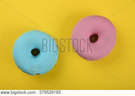 Close Up Two Pink And Blue Glazed Ring Donuts Over Yellow Background, Elevated Top View, Directly Ab