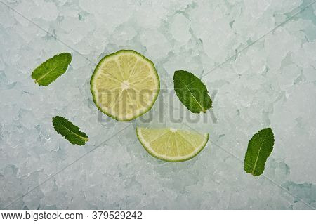 Close Up Fresh Juicy Green Lime Cut Half And Wedge Slice And Mint Leaves Over Background Of Crushed
