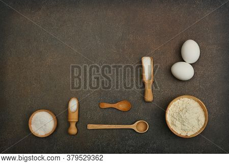 Close Up Flat Lay Of Baking Ingredients On Dark Grunge Stone Table Surface With Copy Space, Flour, E
