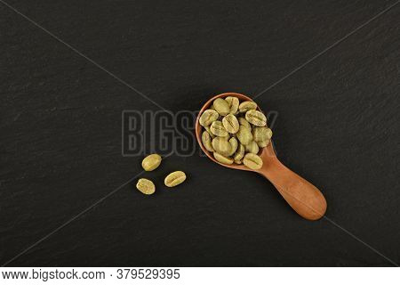 Close Up One Wooden Scoop Spoon Full Of Unroasted Raw Green Arabica Coffee Beans Over Black Slate Ba