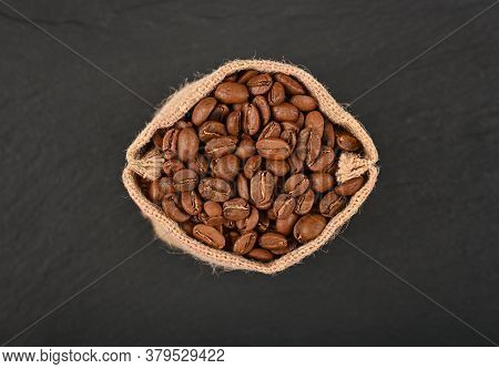 Close Up One Jute Canvas Bag Of Roasted Arabica Coffee Beans Over Black Slate Background, Elevated T