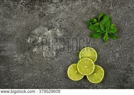 Close Up Heap Of Fresh Green Mint Leaves, Lime Slices And Ice Cubes On Grunge Gray Stone Table Surfa