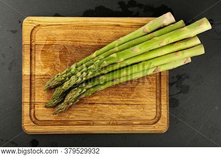 Close Up Bunch Of Washed Fresh Green Asparagus On Wooden Cutting Board With Drops Of Water, Elevated