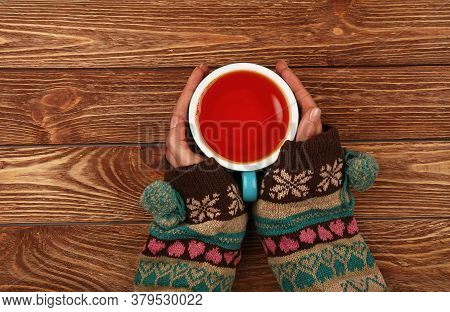 Close Up Two Woman Hands Hold And Hug Big Full Cup Of Black Tea Or Red Fruit Tea Over Brown Wooden T