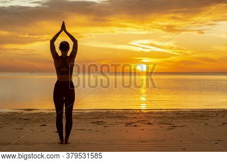 Active Young Woman Doing Yoga On The Beach, Holding A Tree Pose Or Vrikshasana, Standing Balancing Y