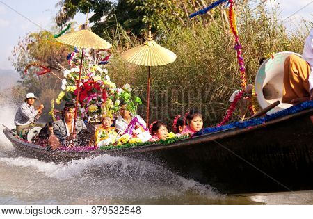 INLE LAKE, MYANMAR - CIRCA FEBRUARY 2018: Widding boat with traditionaly dressed people on the Inle Lake in Myanmar.