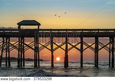 A Pelican Trio Above The Folly Beach Pier Is Silhouetted By A Beautiful Sunrise Over Atlantic Ocean