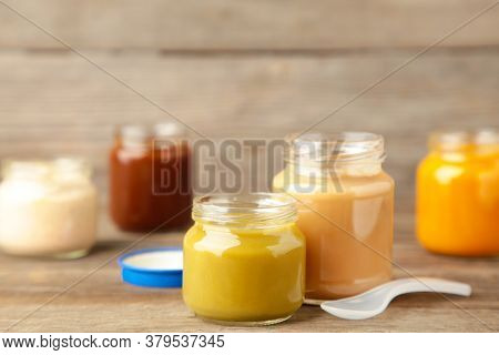 Glass Jars With Nutrient Baby Food On Grey Background. Vegetable Puree With Spoon.