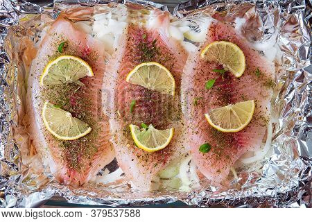 Fillet Of Tilapia With And Herbs, Lemon And Pepper On A Cutting Board Top View