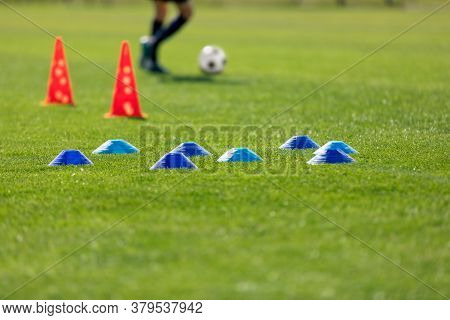 Football Grass Training Field. Soccer Equipment On Grass Pitch. Blue Training Markers And Red Cones.