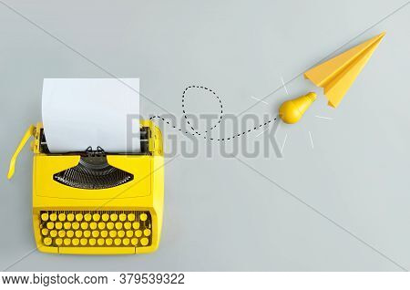 Retro Typewriter With Yellow Paper Airplane, And Light Bulb Inspiration And Innovation
