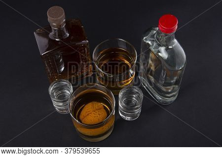 Human Brain In A Glass With An Alcoholic Drink, Against The Background Of Bottles With Alcohol. Alco