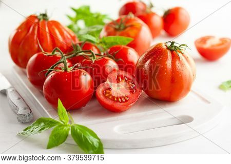 Assorted fresh ripe tomatoes and basil on white board. Healthy food concept. Clean eating