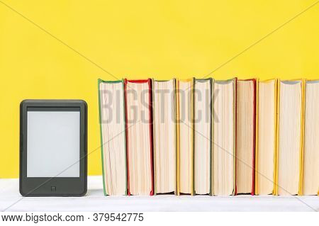 E-learning And Knowledge. E-book Reader And A Stack Of Books On A Yellow Background. Copy Space. Moc