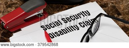 Social Security Disability Claim Concept. An Application Form On The Table Next To A Red Pen And Gla