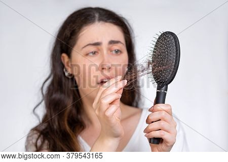 Portrait In A Blur, A Frustrated Brunette Woman Holds A Comb In Her Hands, Cleaning It From A Pile O