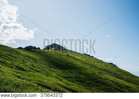 Vivid Green Hill With Rock On Top Under Blue Sky With Clouds. Colorful Green Mountain With Crag In S