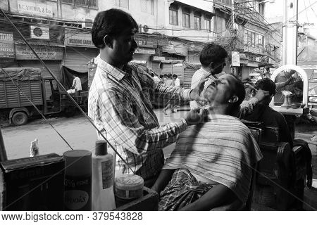 New Delhi, India - Jul 9, 2015: A Sidewalk Barber Gives A Shave To A Client In New Delhi, India. It'