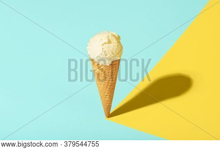Ice Cream In A Waffle Cone With Vanilla, On Blue And Yellow Pastel Background, In Harsh Light. Cold