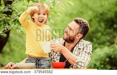 Family Dinner Time. Father And Son Eating Outdoor. Happy Fathers Day. Little Boy With Dad Eat Cereal