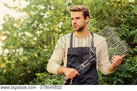 Backyard Barbeque Party. Tools For Roasting Meat Outdoors. Picnic Concept. Handsome Guy Cooking Food
