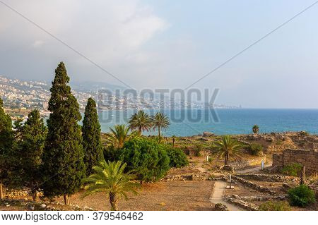 Excavation Of Byblos, Lebanon. Numerous Stone Walls Of Ancient Structures. Beautiful Seascape With B
