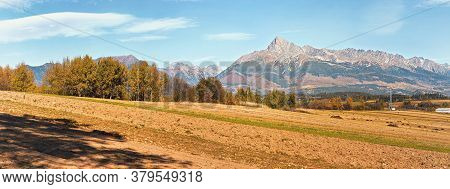 Mount Krivan Peak Slovak Symbol With Blurred Autumn Coloured Trees And Dry Field In Foreground Wide