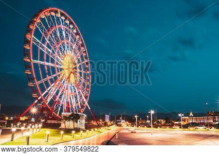 Batumi, Adjara, Georgia. Ferris Wheel At Promenade In Miracle Park, Amusement City Park On Blue Even
