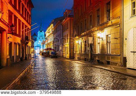 Riga, Latvia. Evening View Of Pils Street With Ancient Architecture In Bright Warm Yellow Illuminati