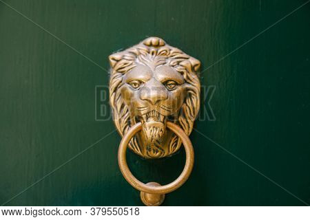 Antique Door Handle On A Green Wooden Door In The Shape Of A Lions Face With A Knock Ring In The Mou
