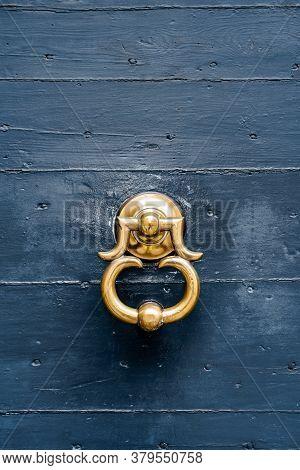Antique Door Handle-ring In Gilding On A Blue Wooden Door.