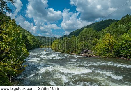 A Whitewater Raft And A Few Kayaks Going Down The Fast Current Of The Ocoee River In Tennessee With