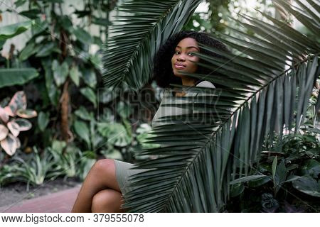 African Woman Model In Tropical Greenhouse. The Portrait Of African American Female Model In Khaki D