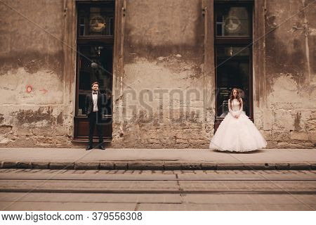 Happy Newlywed Couple On A Walk In Old European Town Street, Gorgeous Bride In White Wedding Dress T