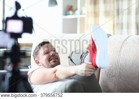 The Guy Lies On The Couch And Pulls Red Sneakers. A Man In His Apartment Is Reviewing New Sports Sho