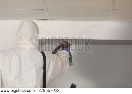 A Builder In Uniform Works With A Spray Gun. An Economical And Effective Way To Paint Walls