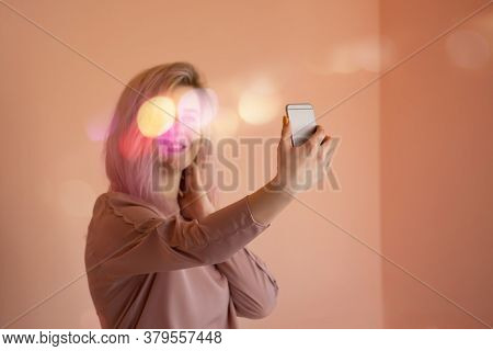 Girl Over Beige Wall Making A Selfie. Smiling Girl Making Selfie Photo On Smartphone.