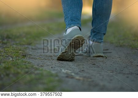 Woman Runner In Jeans And Sneakers. Beauty Woman In Nature And Bright Sunlight.